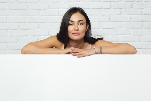 Giovane donna castana che tiene grande bordo bianco in bianco con lo spazio della copia