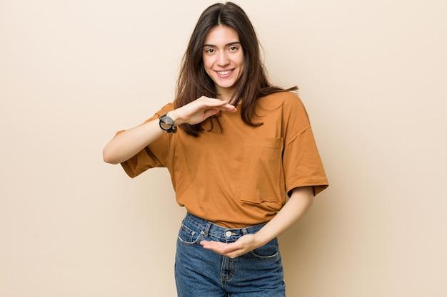 Giovane donna castana che tiene qualcosa con entrambe le mani, presentazione del prodotto
