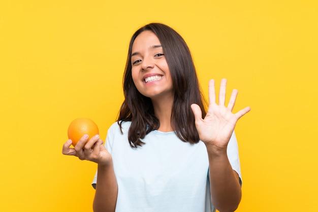 Giovane donna castana che tiene un'arancia che saluta con la mano con l'espressione felice
