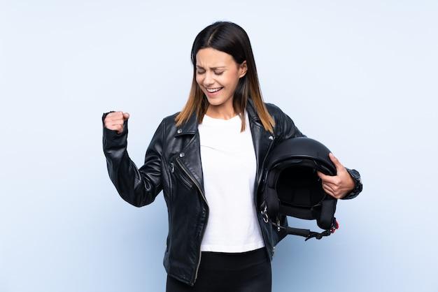 Giovane donna castana che tiene un casco del motociclo sopra la parete blu che celebra una vittoria