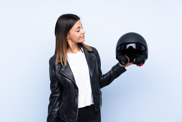 Giovane donna castana che tiene un casco del motociclo sopra la parete blu con l'espressione felice