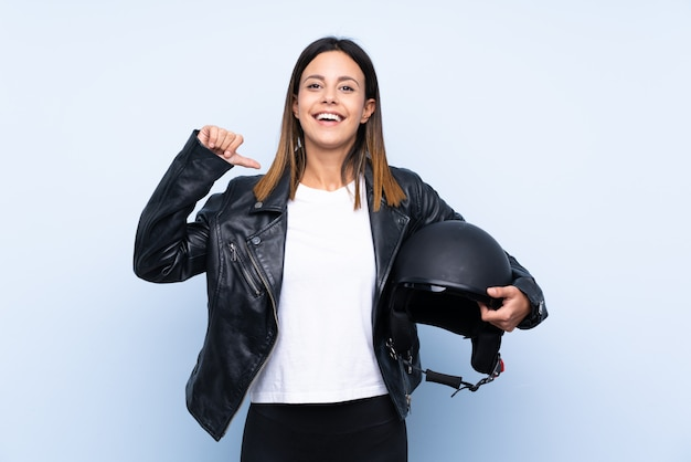Giovane donna castana che tiene un casco del motociclo sopra la parete blu fiera e soddisfatta di sé
