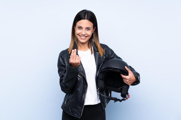 Giovane donna castana che tiene un casco del motociclo sopra la parete blu isolata che invita a venire con la mano. felice che tu sia venuto