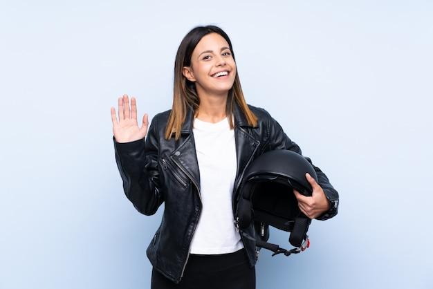 Giovane donna castana che tiene un casco del motociclo sopra la parete blu isolata che saluta con la mano con l'espressione felice