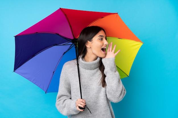 Giovane donna castana che tiene un ombrello sopra la parete blu che grida con la bocca spalancata