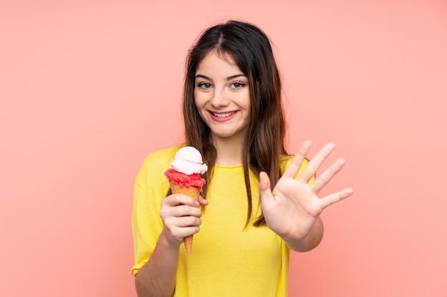 Giovane donna castana che tiene un rosa del gelato della cornetta che saluta con la mano con l'espressione felice