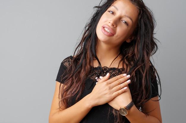 Giovane donna castana che tocca il suo cuore con le sue mani