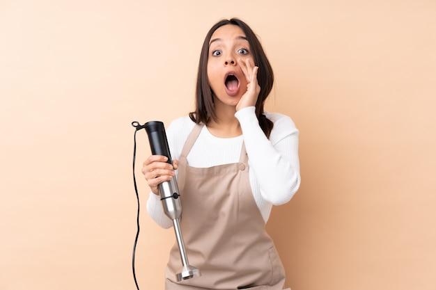 Giovane donna castana che usando il miscelatore della mano sopra la parete isolata che grida e che annuncia qualcosa