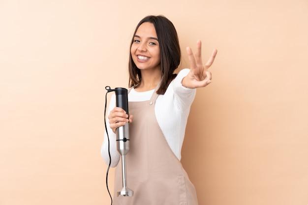 Giovane donna castana che usando il miscelatore della mano sopra la parete isolata felice e contando tre con le dita