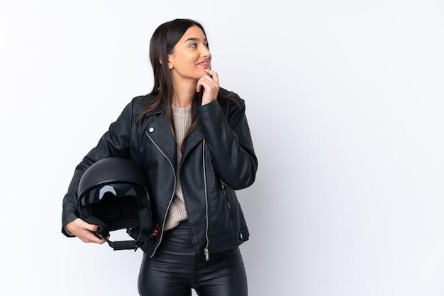 Giovane donna castana con un casco del motociclo che pensa un'idea e che guarda lato