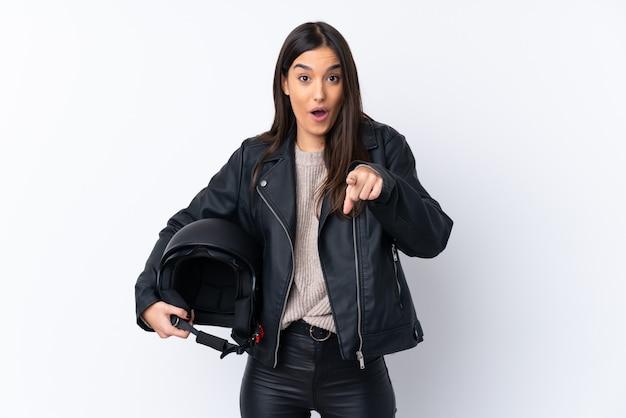 Giovane donna castana con un casco del motociclo sopra la parete bianca isolata sorpresa e indicando parte anteriore