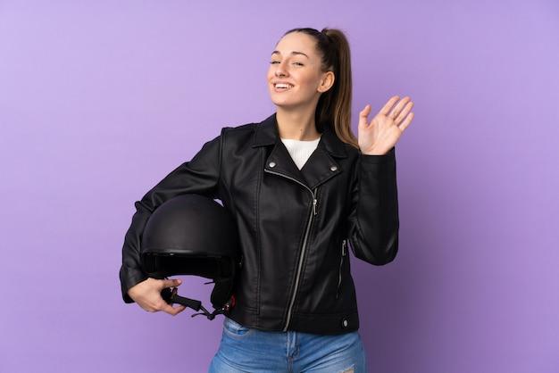 Giovane donna castana con un casco del motociclo sopra la parete porpora isolata che saluta con la mano con l'espressione felice