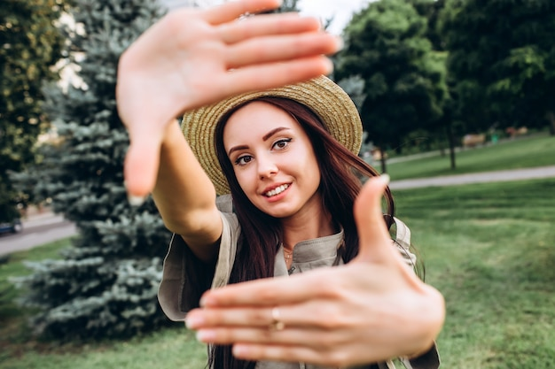 Giovane donna castana dei pantaloni a vita bassa che prende un selfie, mostrante lingua, fronte divertente che posa all'aperto. ritratto del primo piano di una ragazza in un cappello alla moda di estate in un parco.