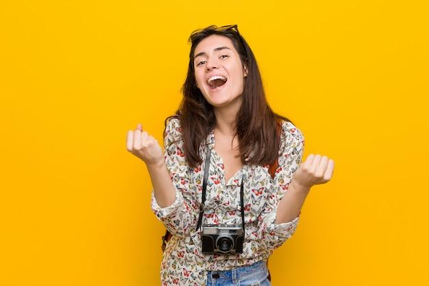 Giovane donna castana del viaggiatore che incoraggia spensierato ed eccitato. vittoria .