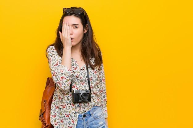 Giovane donna castana del viaggiatore divertendosi coprendo metà del viso con la palma.