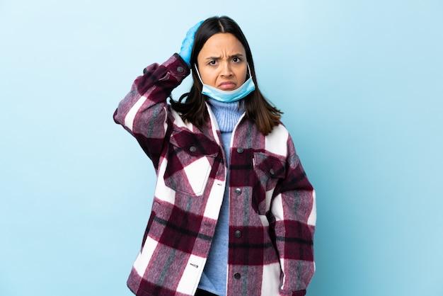 Giovane donna castana della corsa mista che protegge con una maschera e guanti sopra la parete blu con un'espressione di frustrazione e di non comprensione