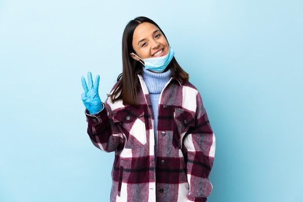 Giovane donna castana della corsa mista che protegge con una maschera e guanti sopra la parete blu felice e che conta tre con le dita