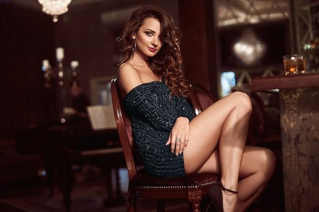 Giovane donna castana di bellezza che si siede al bar