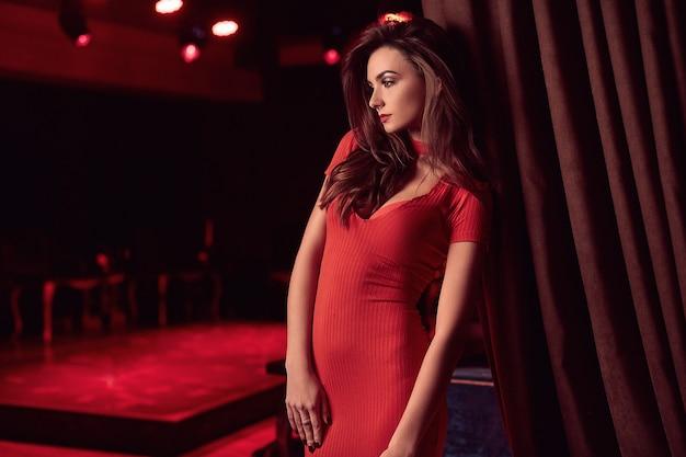 Giovane donna castana di bellezza splendida che porta vestito rosso