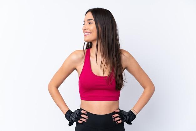 Giovane donna castana di sport sopra la parete bianca isolata che posa con le armi all'anca e che guarda lato