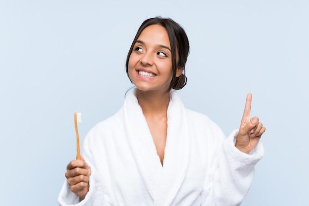 Giovane donna castana in accappatoio che pulisce i suoi denti sopra la parete blu isolata che intende realizzare la soluzione mentre sollevando un dito su