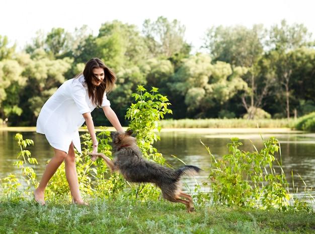 Giovane donna castana in vestito bianco che gioca con il cane su erba il giorno di estate con gli alberi verdi e fiume al fondo