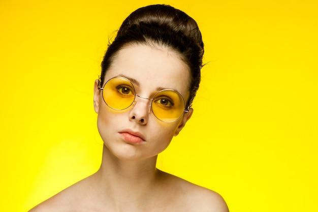 Giovane donna castana in vetri gialli, ritratto su giallo
