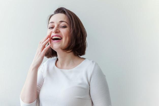 Giovane donna castana positiva felice del ritratto di bellezza su bianco isolata