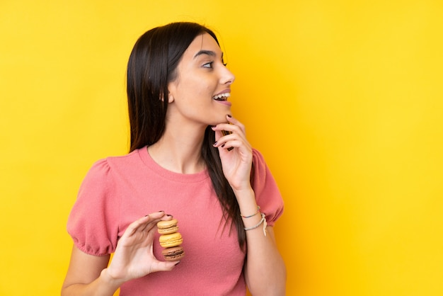 Giovane donna castana sopra giallo che tiene i macarons variopinti e che pensa un'idea