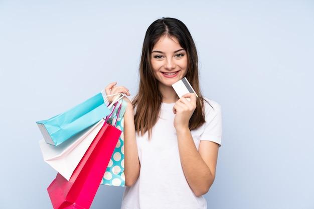 Giovane donna castana sopra i sacchetti della spesa blu della tenuta della parete e una carta di credito