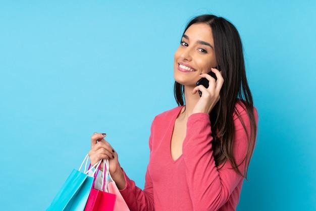Giovane donna castana sopra i sacchetti della spesa blu isolati della tenuta della parete e chiamare un amico con il suo telefono cellulare