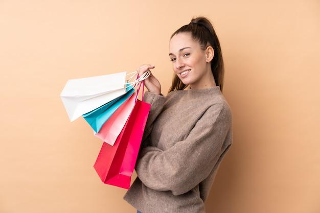 Giovane donna castana sopra i sacchetti della spesa e sorridere isolati di wallholding
