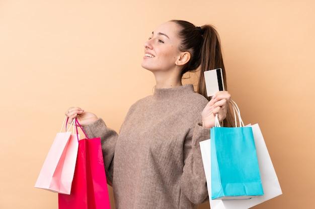 Giovane donna castana sopra i sacchetti della spesa isolati della tenuta della parete e una carta di credito