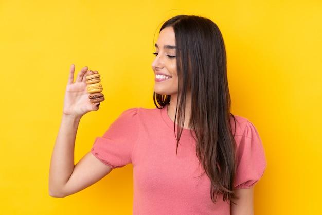 Giovane donna castana sopra la parete gialla isolata che tiene i macarons francesi variopinti e con l'espressione felice