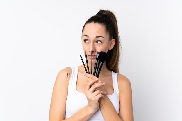 Giovane donna castana sopra la spazzola bianca isolata e cercare di trucco della tenuta della parete