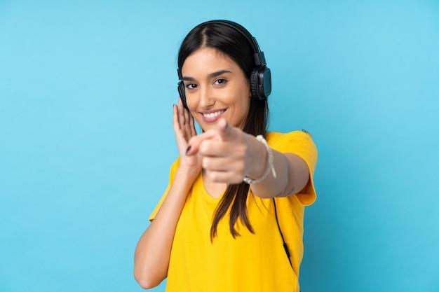 Giovane donna castana sopra musica d'ascolto isolata della parete blu e indicare la parte anteriore