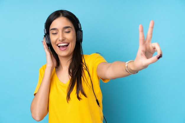 Giovane donna castana sopra musica d'ascolto isolata e cantare della parete blu
