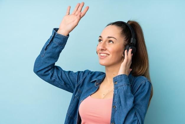 Giovane donna castana sopra musica e ballare d'ascolto isolati della parete blu