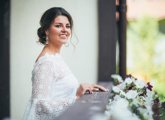 Giovane donna castana sorridente bella della sposa in vestito bianco dal pizzo sul balcone,