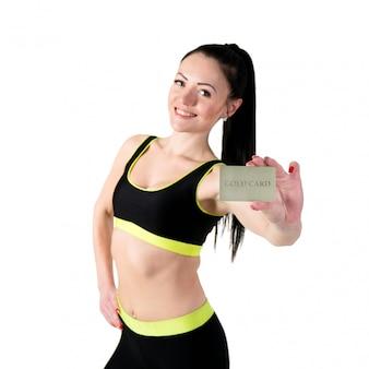 Giovane donna castana sorridente che mostra la carta di credito dell'oro.
