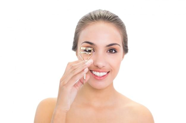 Giovane donna castana sorridente che usando un bigodino del ciglio