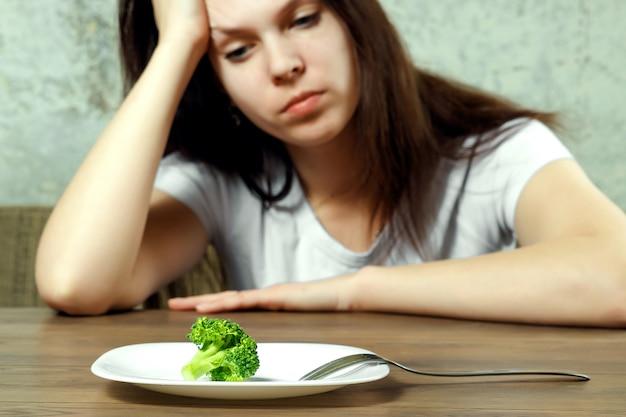 Giovane donna castana triste che mangia una piccola verdura verde sul piatto