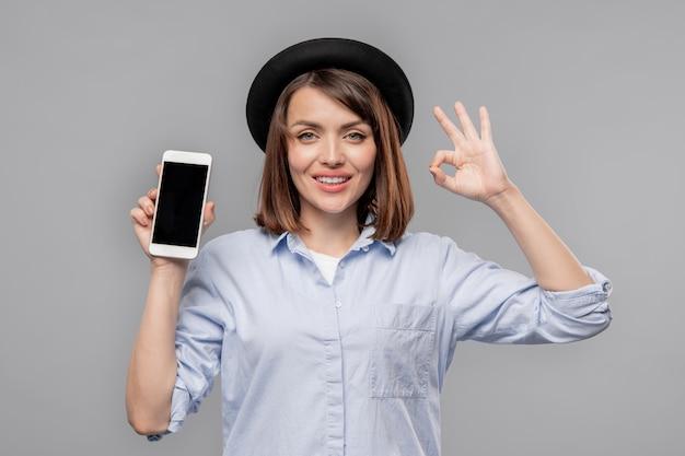 Giovane donna casual che mostra il gesto giusto e promo della vendita stagionale in smartphone