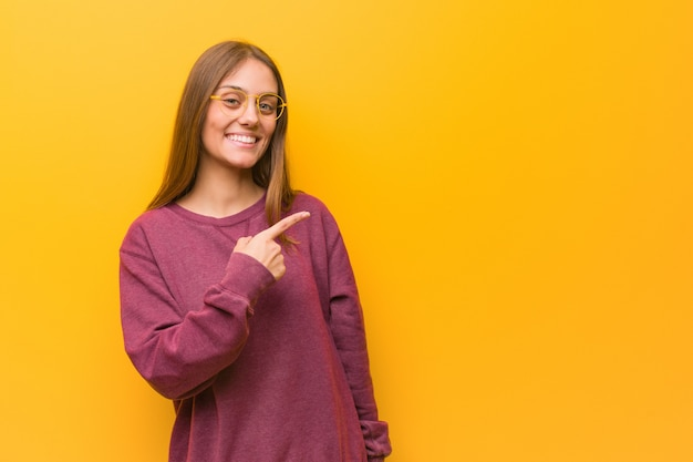 Giovane donna casual sorridendo e indicando il lato