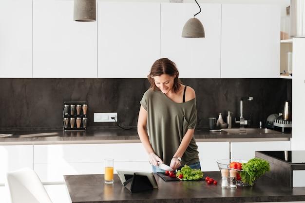 Giovane donna casuale che cucina insalata fresca