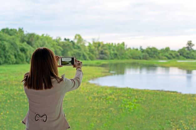 Giovane donna casuale che per mezzo del suo telefono cellulare per catturare le immagini della pianta acquatica su un fiume.