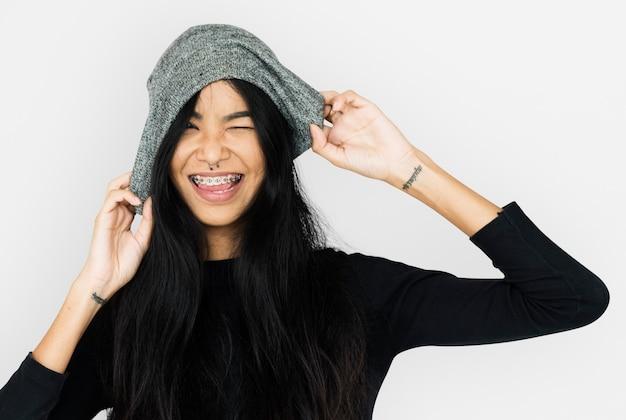 Giovane donna casuale con il berretto della holding del tatuaggio