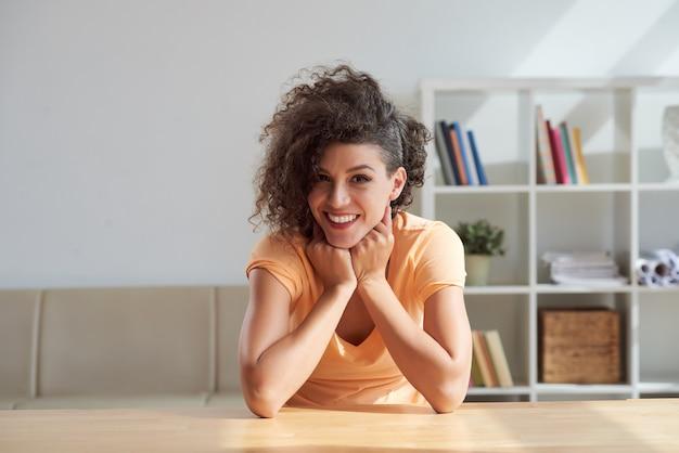 Giovane donna caucasica allegra con capelli ricci che sorride per la macchina fotografica a casa