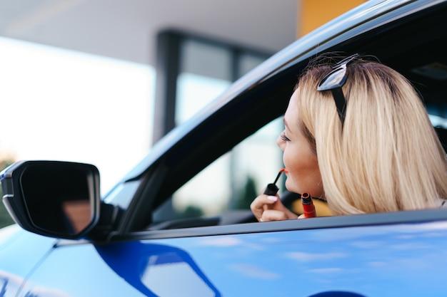 Giovane donna caucasica applicando il rossetto guardando il riflesso nello specchio dell'auto.