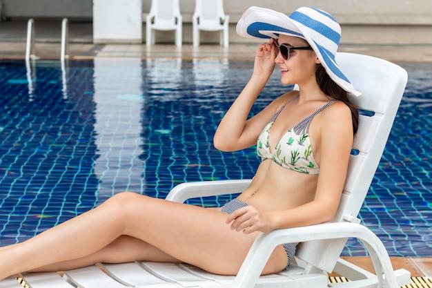 Giovane donna caucasica attraente che si rilassa e che indossa un bikini che si siede sulla spiaggia della sedia vicino allo stagno.
